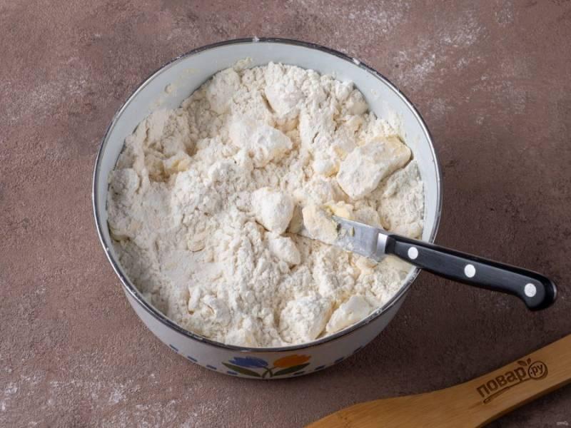 Начните с приготовления теста. Маргарин порубите кусками и выложите в удобную металлическую миску вместе с мукой. Порубите муку с маргарином ножом. Тесто вообще не трогаем руками, только в конце приготовления, когда нужно будет собрать в шар.