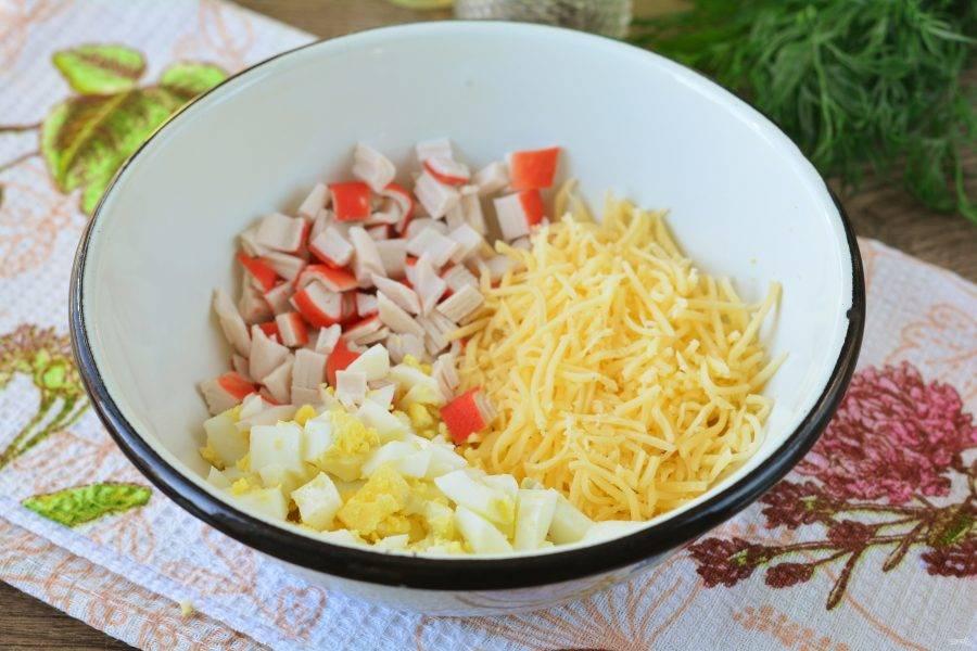 Сложите в миску подготовленные продукты: сыр, крабовые палочки и яйца.