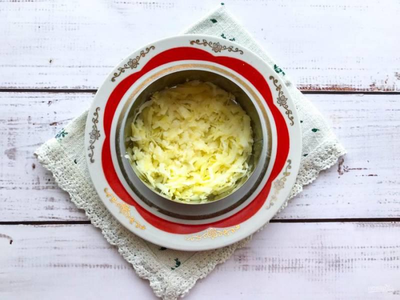 Картофель очистите, натрите на средней терке и выложите на дно тарелки.