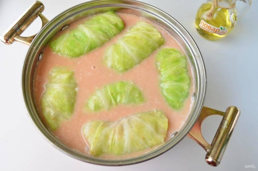 11. Из воды, томатной пасты и сметаны сделайте соус, просто соедините ингредиенты и перемешайте до однородного состояния, посолите и поперчите по вкусу. Залейте соусом голубцы. Тушите на медленном огне 50-60 минут.