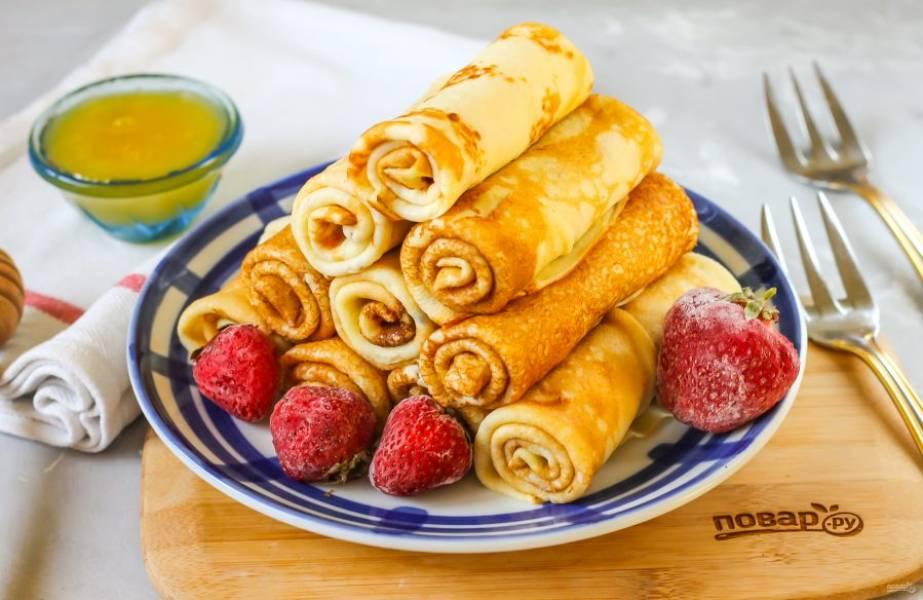 Готовые блины выложите на тарелку и сверните края каждого блина, а затем скатайте его рулетиком. Выложите на блюдо и подайте с ягодами, фруктами, соусами или топпингом, медом.