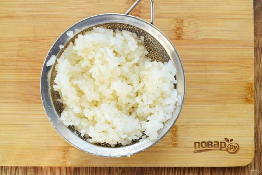 Рис залейте водой (1:2), посолите, отварите до полуготовности, откиньте на сито.