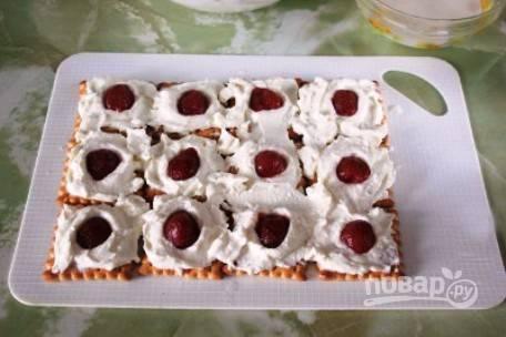 Дальше на печенье аккуратно выкладываем творожную массу и сверху — половинки клубники на каждое печенье.