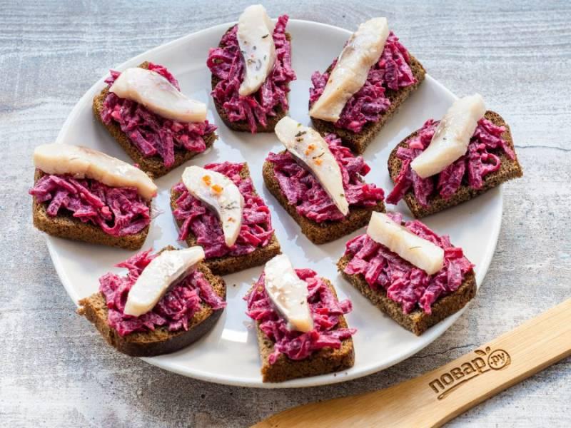 Сверху на каждый бутерброд выложите по кусочку филе сельди.