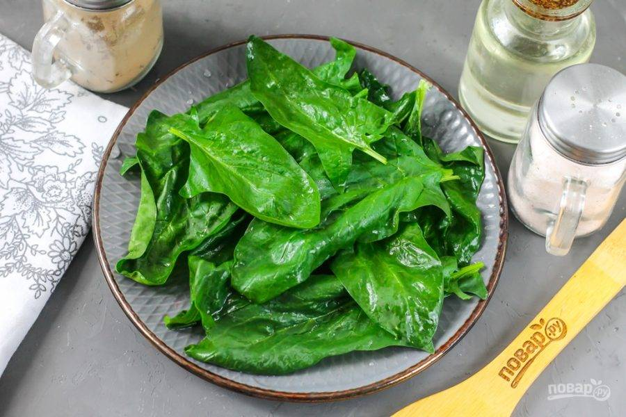 Пучок шпината разберите, промойте каждый лист в воде и срежьте с них стебли. Обмакните бумажными салфетками, удаляя лишнюю влагу и выложите на тарелку. Можно ошпарить зелень кипятком или подержать шпинат в кипятке около 2-3 минут — он станет более мягким.