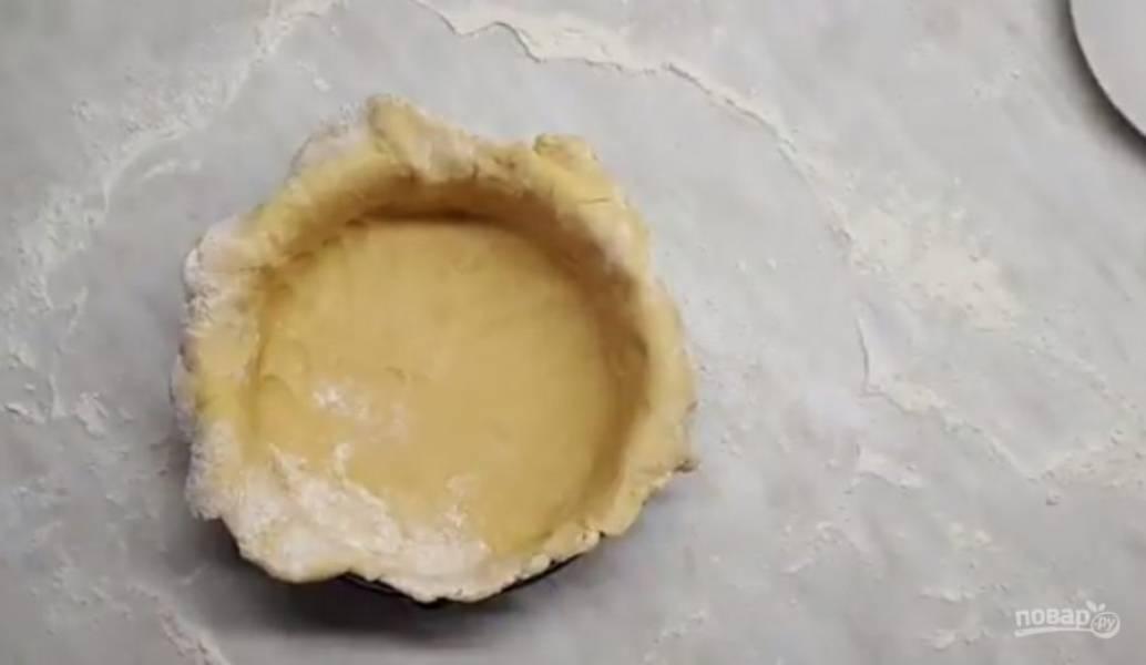3.  Тесто раскатайте в тонкий круг диаметром 30-35 см и выложите в форму, сформировав бока. Поставьте тесто в холодильник на 20 минут.