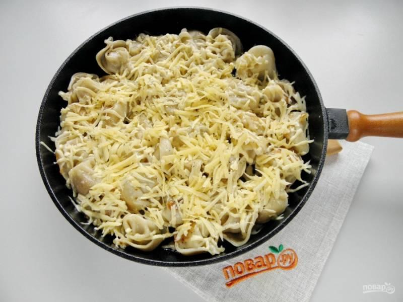 Натрите сыр на крупной терке. Распределите сыр по горячим пельменям. Закройте крышкой сковороду и оставьте пельмени на 5-6 минут.