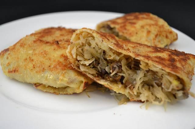 3. Капусту с грибами откиньте на дуршлаг. Ложкой выложите начинку на блинчик и заверните конвертиком. Затем блинчики надо обжарить в сковороде на масле. Гораздо вкуснее будет, если вы такие фаршированные блинчики сначала окунете во взбитое яйцо, а затем в сухари и обжарите на масле.