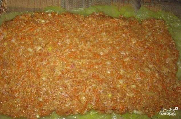 Теперь нужно нанести фарш на выложенные капустные листья равномерным слоем. Удобнее всего это делать лопаткой или столовой ложкой. На слой насыпьте соль, перец и приправы по вкусу.
