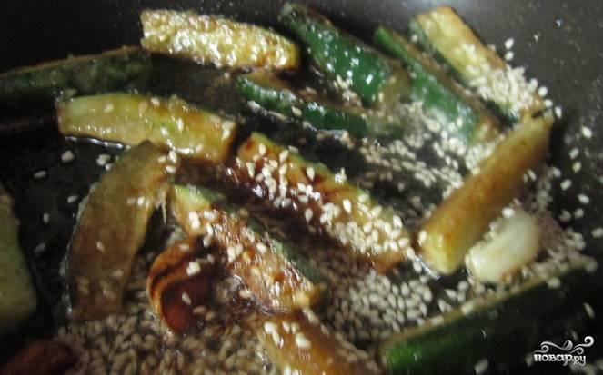 3.По прошествии двадцати секунд добавьте огурцы, не переставая мешать, в сковороду насыпьте кунжут. Я также добавляю немного мелко нарезанного болгарского перца.
