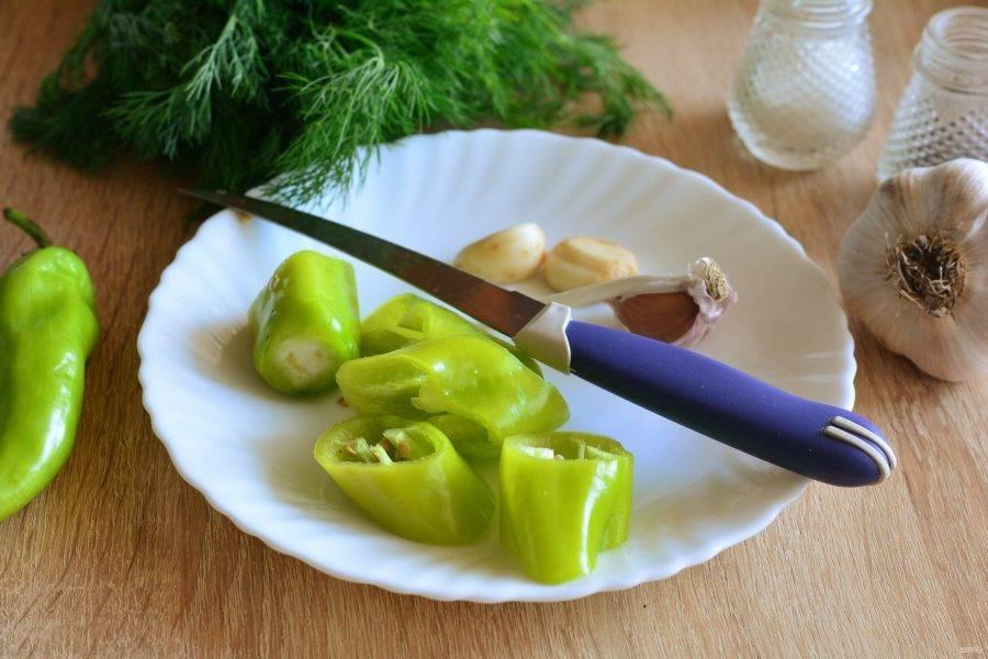 Нарежьте кусочками острый перец и почистите чеснок.