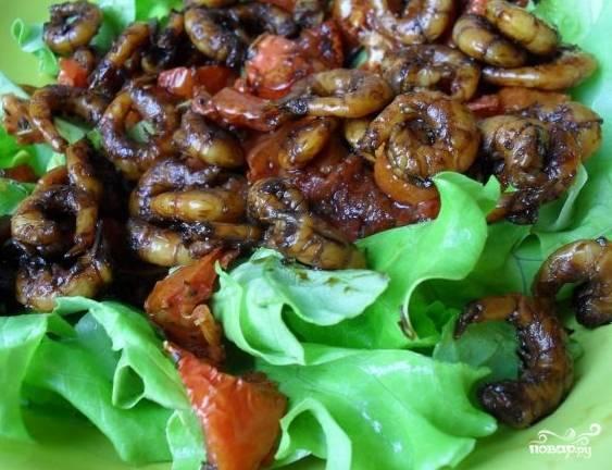 Положите на блюдо крупные кусочки листьев салата (их можно и руками нарвать). Затем порежьте вяленые помидоры, сложите их на листья салата. Теперь добавьте обжаренные креветки. Сверху накрошите кусочки зелёного лука и полейте всё это лимонным соком и оливковым маслом. Посолите и аккуратно перемешайте, не затрагивая салатные листья.