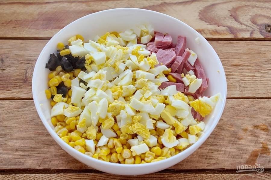 В салатнике соедините ветчину, грибы, маслины, отварные куриные яйца и добавьте кукурузу консервированную.