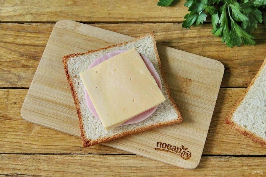Положите на каждый кусочек хлеба кружок ветчины, на ветчину положите нарезанный сыр и сверху накройте начинку еще одним кусочком хлеба.