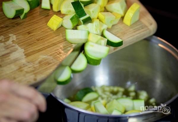2. Вымойте, обсушите и нарежьте кабачки. Можно использовать и кабачки, и цукини, например. Отправьте в кастрюлю. Обжарьте на среднем огне, помешивая.
