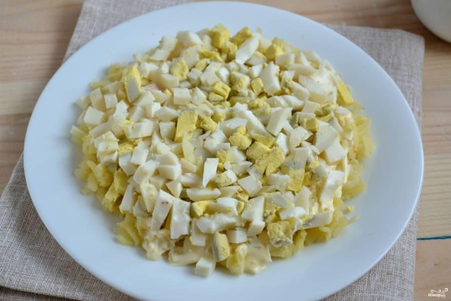 Сверху выложите мелко нарезанные яйца и тоже смажьте майонезом.
