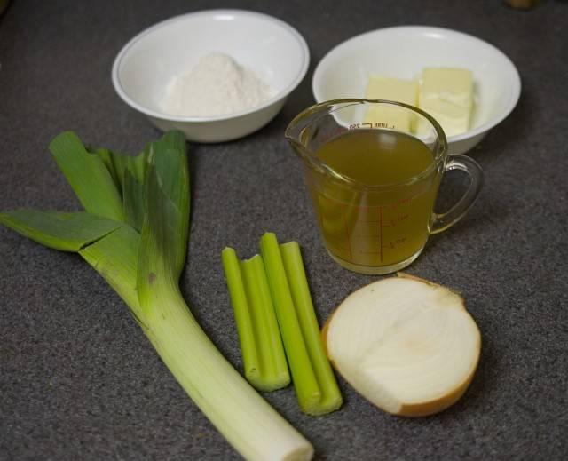 Вам потребуется около 1 / 3 чашки (70 г) муки, 4 унций (110 г) сливочного масла, 1 чашка (235 мл) куриного бульона, 4 унций (110 г) кубиками лук (около 1 / 2 большого желтого лука ), 2 унции (55 г) сельдерея, 2 унции (55 г) лук-порей, 7 чашек (1,65 л) цельного молока (не показан).  Вам также необходимо иметь от 12 до 16 унций (340 до 450 г) шампиньонов, 1 / 4 чайной ложки (0,4 г) сушеного молотого эстрагона, 1 / 2 чашки (120 мл), сливки, лимонный сок, соль, и перец.