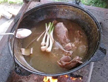 А в казан отправляем чеснок со стеблями, зиру и соль, перемешиваем все и варим мясо еще 15 минут.