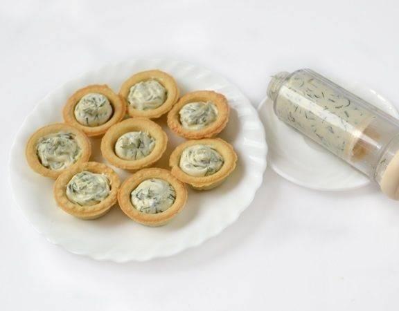 4. Тарталетки заполнить сырной начинкой практически до верха. Сделать это можно с помощью кондитерского шприца - получится более аккуратно. Впрочем, тарталетки с семгой и сыром в домашних условиях можно наполнить и обыкновенной ложкой.