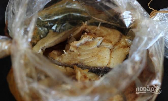 Разогрейте духовку до ста восьмидесяти градусов, положите в нее рыбу в рукаве для запекания. Готовьте блюдо на протяжение сорока минут. Готовую рыбу подавайте с веточками петрушки.