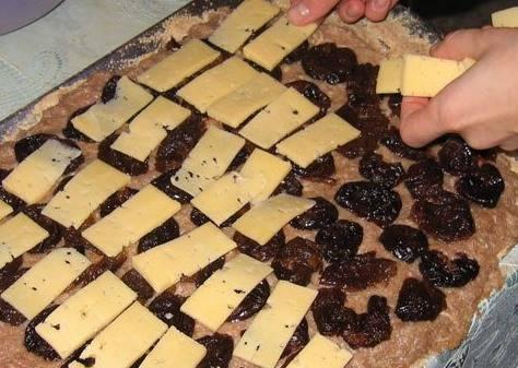 В глубокую посуду выкладываем фарш, добавляем соль, перец, мелко рубленный лук и яичный желток. На противень выкладываем фольгу, смазываем ее маслом. Сверху выкладываем подготовленный фарш. На фарш выкладываем запаренный 15 минут чернослив без косточек, сверху выкладываем нарезанный слайсами сыр.
