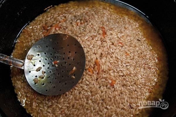 Сначала разровняйте рис, после чего соберите его горкой и оставьте, пока не выкипит вода.