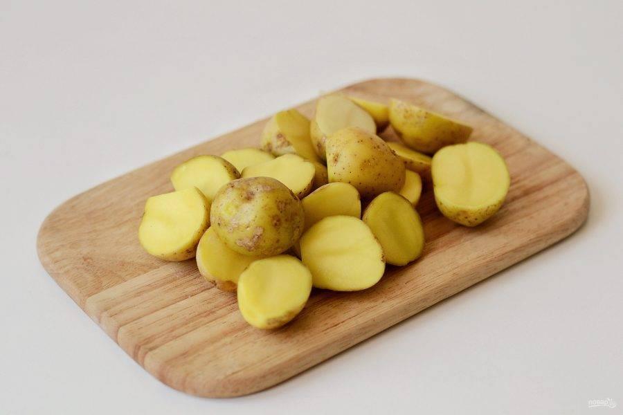 Картофель промойте, затем нарежьте на половинки. Если кожура тонкая, его можно не чистить.