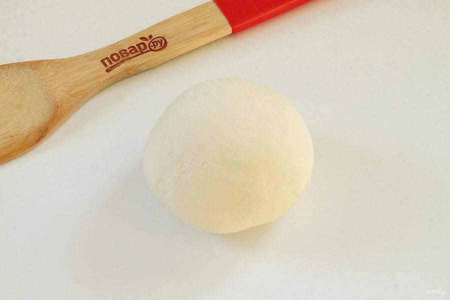 В просеянную муку добавьте щепотку соли, столовую ложку растительного масла и понемногу вливая кефир, замесите тесто. Накройте тесто полотенцем и оставьте на 30 минут.
