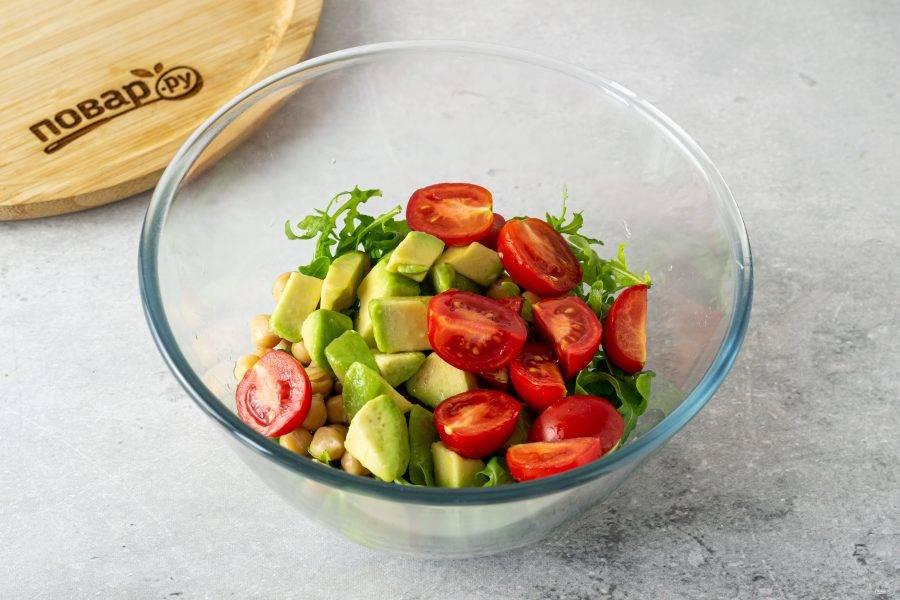 Авокадо очистите от кожуры, удалите косточку. Нарежьте кубиками. Помидоры черри разрежьте пополам. Добавьте подготовленные ингредиенты в миску.