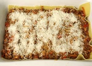 На листы выложите половину фарша, затем томатную смесь, посыпьте все тертым сыром.