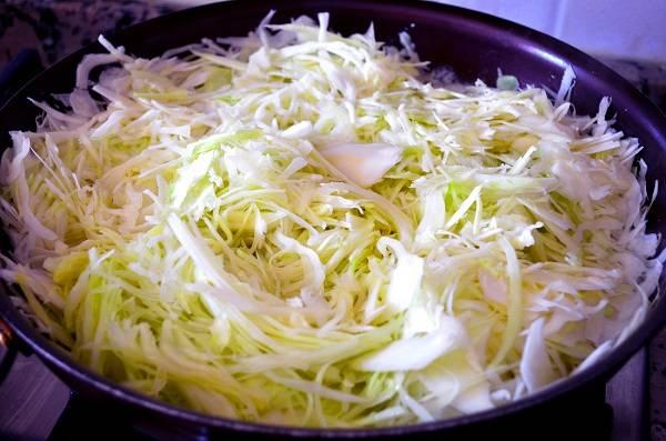 3. Примерно столько времени и понадобится для приготовления начинки. Для начала отправьте вариться яйца, затем остудите их и очистите. Этот простой рецепт нежного пирога с капустой можно дополнить также отварной морковью или рисом, например. Капусту мелко нашинкуйте и отправьте на сковороду с растительным маслом. Добавьте сахар, щепотку соли и молоко. Оставьтена 10-15 минут, пока капуста не станет мягкой, на небольшом огне.