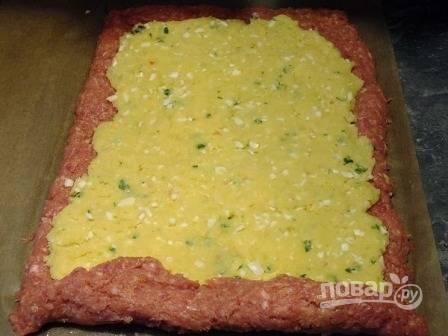 Выкладываем фарш на пищевую пленку или влажное вафельное полотенце прямоугольным слоем примерно в 1 см толщиной. Размер мясного пласта у меня примерно 45 на 25 см. И теперь равномерно и плотно раскладываем картофельную начинку.