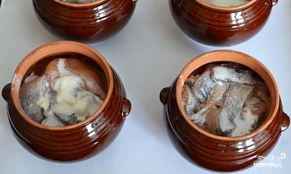 5. Стакан сметаны соедините с половиной стакана чистой воды. Добавьте соль, перец и перемешайте. Распределите соус равномерно по горшочкам.