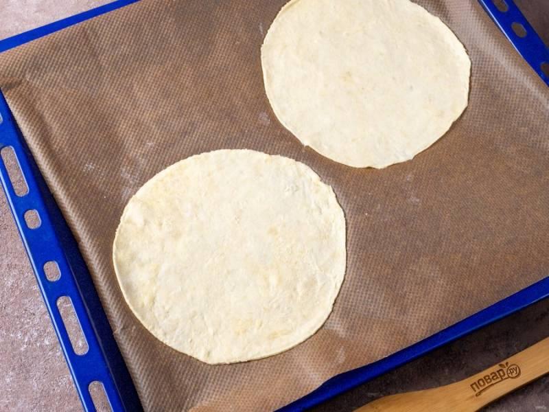 Пока крем остывает, продолжим работу с тестом. Если вам хочется высокий торт из 11-12 коржей, то равняйте их по плоской тарелке диаметром 19 см. Если же хотите широкий торт с 7-8 коржами, то равняйте по тарелке диаметром 25 см. Я выбрала первый вариант. Поверхность на которой будете раскатывать, и скалку, постоянно припыляйте мукой. Возьмите один шар теста (остальные пока можно оставить в холодильнике), раскатайте тонко, примерно 2 мм. толщиной и вырежьте корж ножом прикладывая тарелку.