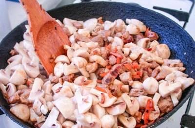 Грибы нарезаем четвертинками, добавляем в мясо и обжариваем все вместе, пока сок с грибов не испарится, почти полностью. Перемешиваем, солим и перчим по вкусу.