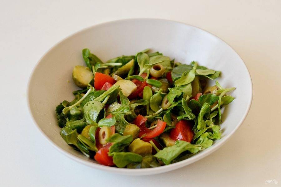 Заправьте салат лимонным соком и оливковым маслом. Посолите и поперчите по вкусу. Перемешайте.