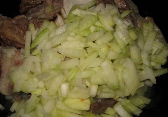 Как только мясной сок от баранины выкипит, и мясо начнет поджариваться, перекладываем его в казан, солим и добавляем репчатый лук. Жарим все на среднем огне, пока лук не станет мягким.
