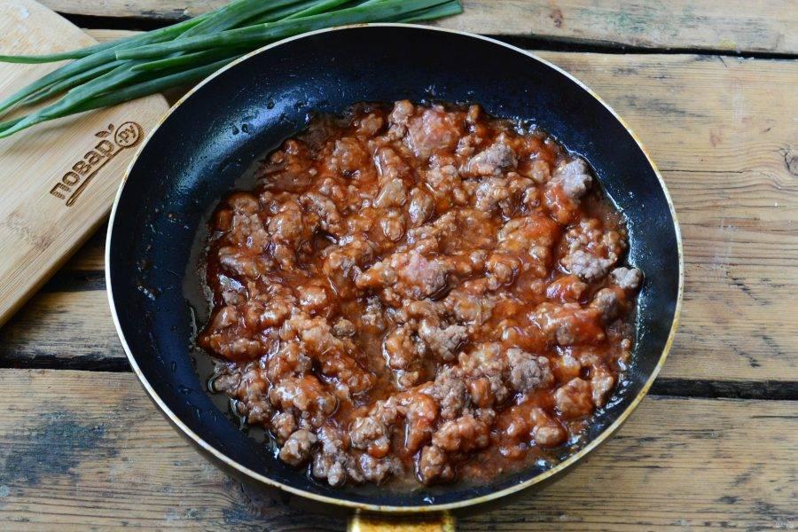 Начнем с приготовления мясного соуса. Фарш отправьте в сковороду с разогретым растительным маслом и жарьте на медленном огне, часто помешивая, 5-7 минут. Затем добавьте томатный соус, посолите и поперчите по вкусу, перемешайте и готовьте еще несколько минут.