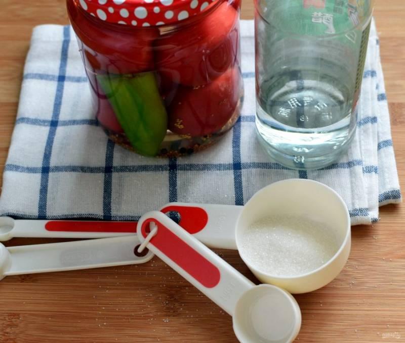 Затем воду слейте в кастрюлю, добавьте соль и сахар. Доведите до кипения и снова залейте в банки.