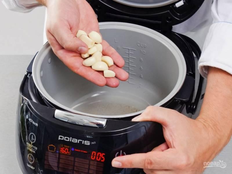 2.Установите чашу мультиварки, налейте в неё растительное масло и включите режим «Мультиповар», установите 160 градусов и отправьте в разогретую чашу чеснок, готовьте его пять минут.