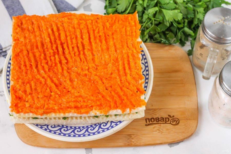 Кусочки слабосоленой сельди измельчите, нарежьте промытые стебли зеленого лука и выложите на второй корж, распределите равномерно. Выложите третий корж и обмажьте его морковной массой.