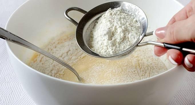 2. Добавить около 1 стакана сметаны и продолжать взбивать. Муку просеять вместе с разрыхлителем и постепенно всыпать в тесто.