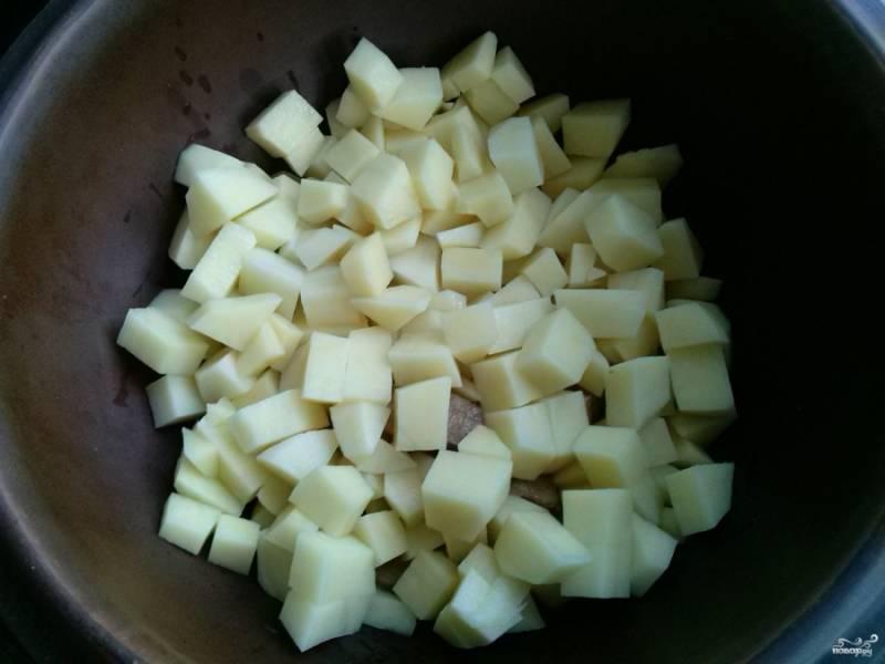 Картофель нарежьте кубиками и отправьте к мясу в горшочек.