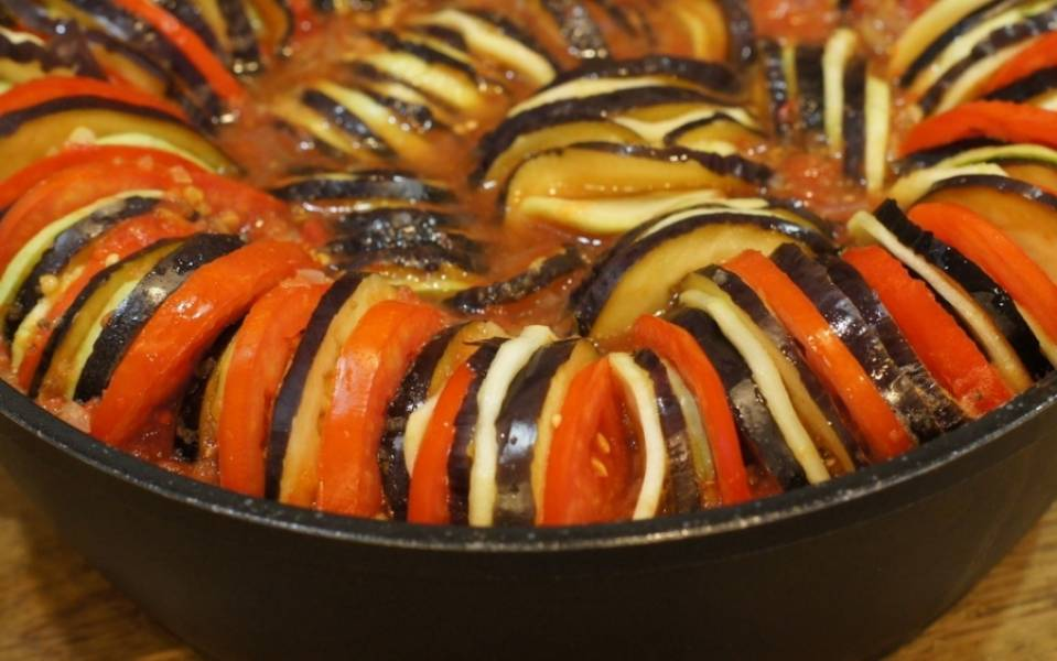 Теперь по кругу выкладываем в форму, где будем выпекать запеканку, кольца баклажана, кабачка и помидора, чередуя их. Заливаем овощи приготовленным соусом.