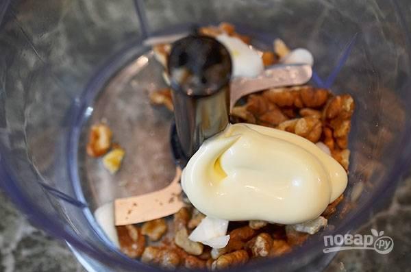 В чашу блендера положите орехи, чеснок, сыр и майонез.