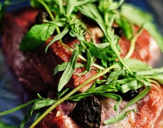 Выкладываем нашпигованное мясо на лист фольги, сверху кладем чернослив и веточки мяты и тархуна.