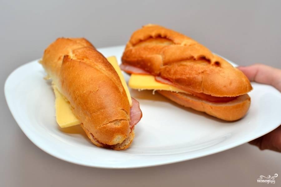 Сложите на нижнюю половинку багета ветчину и сыр. Накройте. Вот у вас и получился багет с ветчиной и сыром.