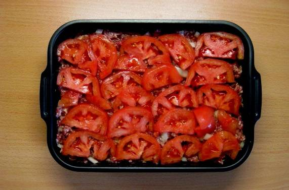 5. Нарезать помидоры тонкими кружочками и выложить сверху мяса. Этот простой рецепт фарша с помидорами и сыром можно дополнить также небольшим количеством томатного соуса (можно свежего) для большей сочности. Подсолить немного сверху.