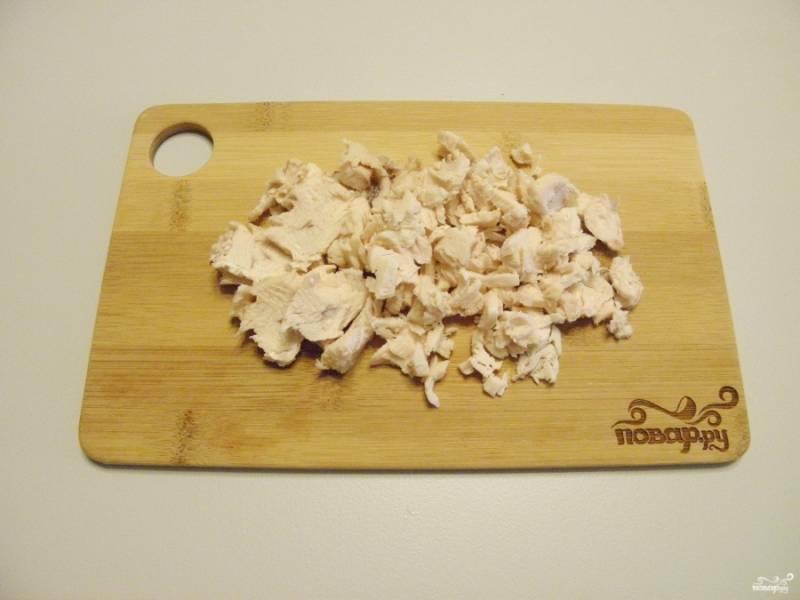 Остывшее куриное филе порежьте тонко поперек волокон.