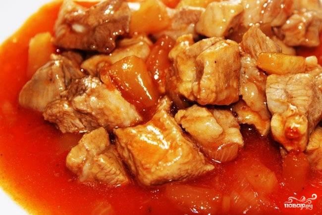 3. В миске смешиваем сок из консервированных ананасов, уксус, томатную пасту и сахар, перемешиваем до однородной консистенции и вливаем к мясу. Бросаем туда ананасы, солим и перчим, накрываем крышкой и тушим на среднем огне пятнадцать минут.